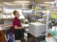 Foodservice staff prepares trays for meal delivery service.